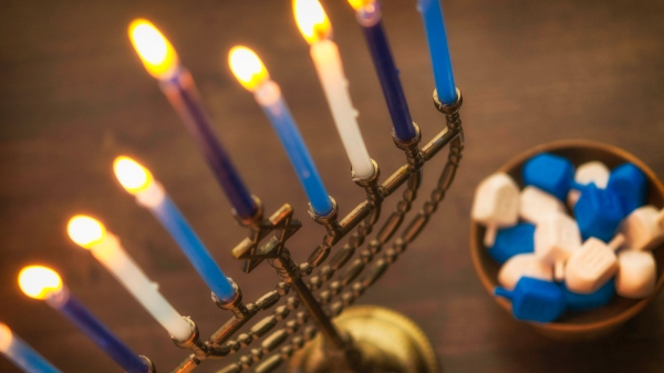 Menorah with burning candles and dreidel. Hanukkah preparations
